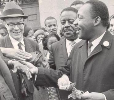 April 22, 1965: The wife of Rev. Virgil Woods (not visible) presents a flower to Dr. Martin Luther King, Jr. Bobby Woods, the Reverend's son, and the Reverend Woods, crowd around Dr. King.