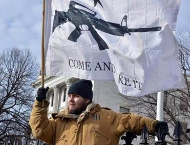 A man who identified himself as Nick M. held a flag bearing the image of an assault rifle at a rally against gun control.