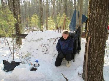 Jacob Ballin, an Arlington High School student, crouches near the shelter he built in Townsend State Forest in north central Massachusetts as part of a wilderness survival experience in early January.