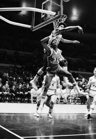 Julius Erving of Massachusetts defends his basket against North Carolina's Bill Chamberlain in National Invitational Tournament in Madison Square Garden.