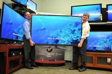 At the George Washington Toma TV store, owner George Toma (left) and salesman Richard Shuman moved a 64-inch TV.