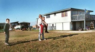 The Gautreaux children play in the yard of the family home in Grand Isle, La.