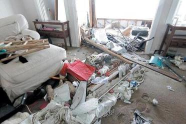 Debris is piled up in a home that was hit by a wave and flooded in Salisbury on Saturday.