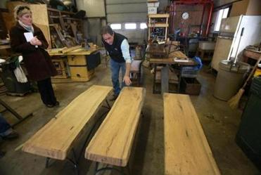 Stephanie Blunt (left) and Brett Stevens (right) are pictured with not quite finished benches made of wood from reclaimed USS Constitution timbers dug up from the Charlestown Naval Yard in 2010.
