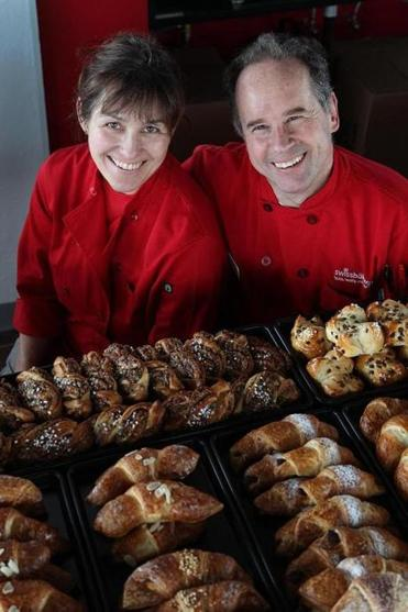 Pretzel bread and rolls (left) and blueberry Berliners (right) at Swissbakers, a bakery owned by Helene and Thomas Stohr (below), who grew up in Switzerland.
