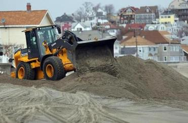 A loader in Winthrop piled beach sand to form a makeshift berm to protect oceanfront homes on Yirrell Beach.