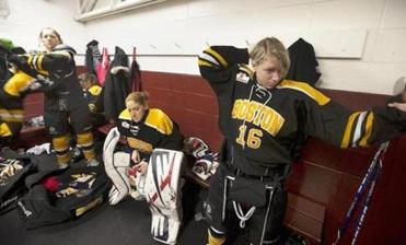 Molly Schaus (seated) and Katka Mrazova get ready with teammates in the tight quarters of their locker room.