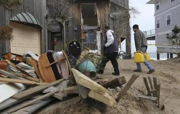 Tim Santiago and Kevin Baez move items from Bob Connors's home (at right) to a neighbor's garage on Plum Island.