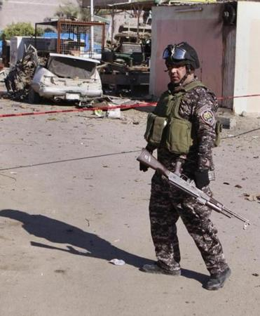 A police man stands guard at the scene of a car bomb attack in Baghdad on Tuesday.