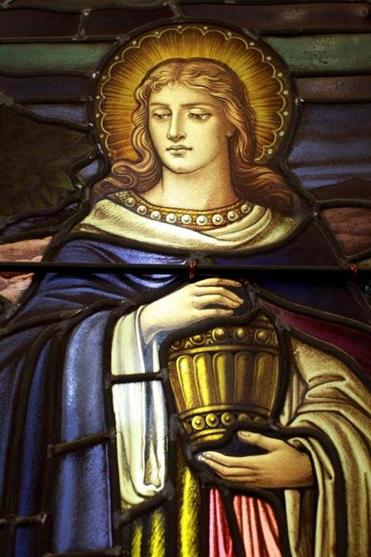A stained glass depiction of St. Mary Magdalen at church.