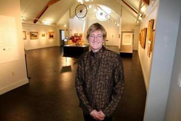 Catherine Amidon, director of the Museum of the White Mountains, stands in the large exhibition gallery.