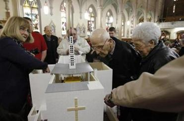 Parishioners look inside a replica of the closed St. Joseph Church made entirely from legos at St. James Church.