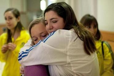 Mary Solomon, a volunteer at the finish line, embraced sorority sister Briana Simicic at a Northeastern University vigil.