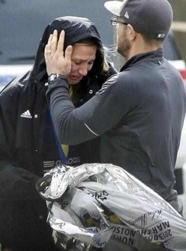 An unidentified Boston Marathon runner was comforted as she cried in the aftermath of the bombing.