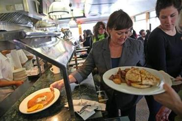 A day after the police search locked down Watertown, owner Daryl Levy handed out plates of food at the packed Deluxe Town Diner on Saturday.