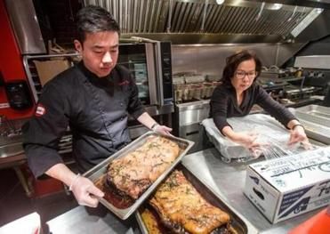 Chris Young and his aunt, Rose Young, prepare New York strip steaks for sandwiches at Wichit on Newbury Street.