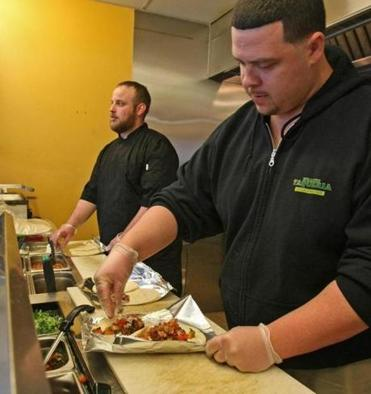 Roxanne's Taqueria partners Jesse Rosen (left) and Josh Katz work the counter making dishes such as ancho trout over lettuce and pico de gallo, and a Sonoran Dog.
