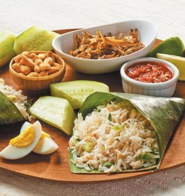 Coconut rice anchors a popular Malaysian breakfast that includes egg, cucumber, peanuts, and more.