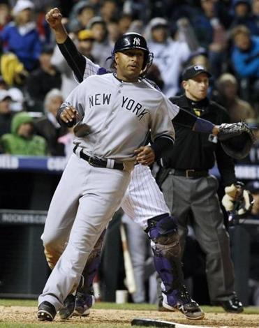 Vernon Wells crosses the plate to score the go-ahead run for the Yankees at Coors Field.