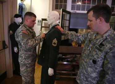 Army Sgt. First Class Daniel Fahey (left) and Army Staff Sgt. Joshua Curtis are helped with the display.