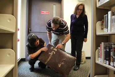 Left to right, Margo Steiner, Chris Mauriello, and Harriet Wacks examined a suitcase donated to the center.