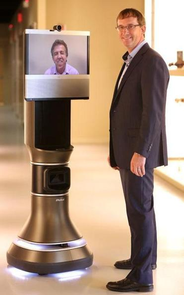 Colin Angle, CEO of iRobot, with the Ava 500. Youssef Saleh, an iRobot vice president, is seen on the display screen, which is a Cisco product.