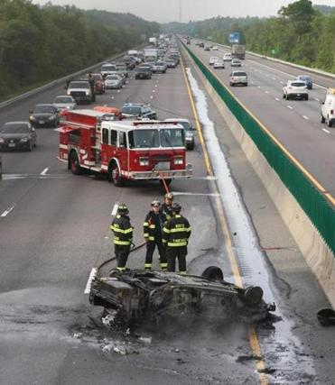 A car rolled over and burst into flames Monday on Route 24 in Brockton, The driver was treated for minor injuries.