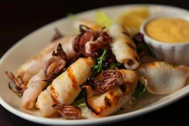 The calimari in gratella. or grilled squid, is served over greens with lemon and mustard sauce.