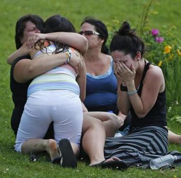 People wept Sunday near a school that was sheltering those who were forced to leave homes in Lac-Megantic.
