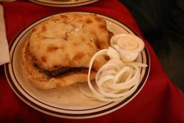 Cevapi consists of lepini — a kind of flatbread — and sausages with sour cream and sliced onions.