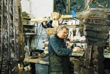 Sculptor Dimitri Hadzi (1921-2006) in his East Cambridge studio in 2003, adding patina to bronze.
