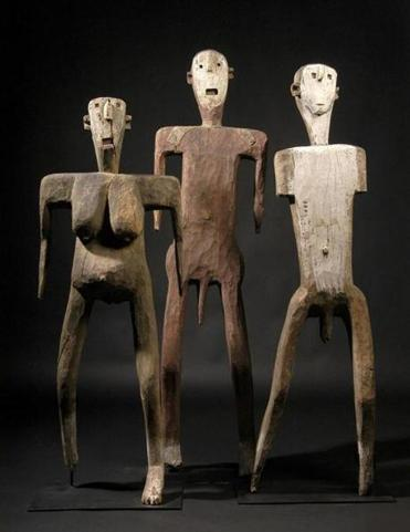 Sukuma dance figures (52, 60, and 56 inches tall) made of wood, metal, and pigments.