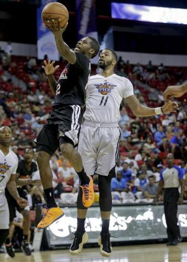 The Raptors' Dwight Buycks lays in two points against the Suns' Markieff Morris during a summer league game.