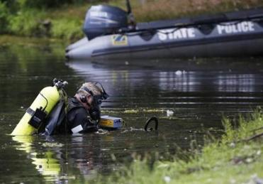 A Connecticut State Police officer searched Pine Lake in Bristol, Conn., for evidence Monday.