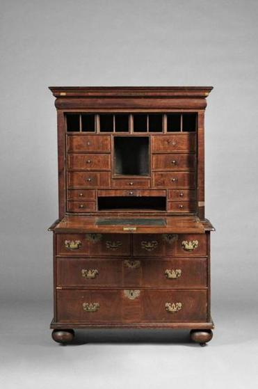 At Skinner's Americana Auction next Sunday, this 18th-century William & Mary fall-front desk with a complex interior of compartments and drawers is expected to bring $30,000-$50,000. Late-18th-century black ladder-back armchair with its early surface but imperfections is from the John T. Kirk Collection; its estimate is $1,000-$1,500. Circa 1810 mahogany-inlaid banjo clock patented by Simon Willard is one of six clocks deaccessioned by Old Sturbridge Village from the J. Cheney Wells Collection; its estimate is $2,500-$3,500. Portrait of a young man with ginger-colored hair by folk artist Ammi Phillips will be offered with a $15,000-$25,000 estimate.