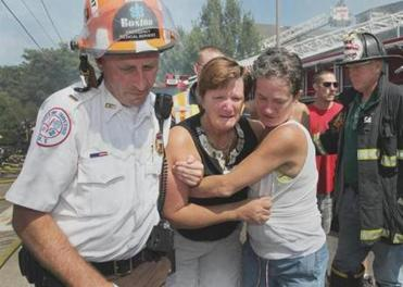 An EMT escorted distraught residents at the scene.