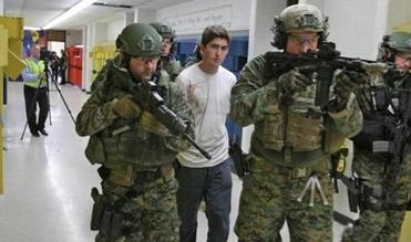 "SWAT team members lead ""suspect"" Brett Harvey out of the old East Bridgewater High School as part of the scripted training scenario for local law enforcement personnel."