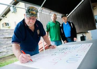 "Army veteran Jim Haskell added his name to the signatures on a board that reads ""Veterans and Citizens against Big I's."""