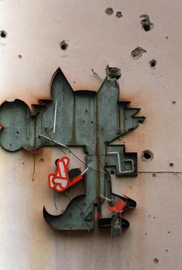A sign depicting Wucko, the mascot of the 1984 Winter Olympics, hangs in disrepair on a Sarajevo building. The destroyed sign is one of the few remaining symbols of the Winter Games held there.