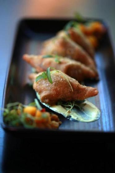 At Opus, samosa-esque turnovers are filled with curried potato.