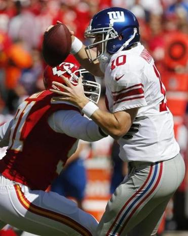 Giants quarterback Eli Manning, here fending off Chiefs linebacker Tamba Hali, had another subpar day for winless New York.
