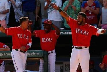 Manager Ron Washington (center) leads the cheers after the Rangers scored in the sixth.
