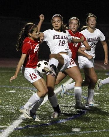Dedham High School senior Libby Masalsky (18) and Milton High midfielder Sophie Cousineau (13) fight for possession during their soccer match in Dedham on Tuesday night.