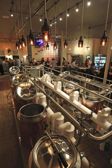 Amateur beer-makers use the copper-jacketed kettles at Hopster's in Newton to make their own brews.