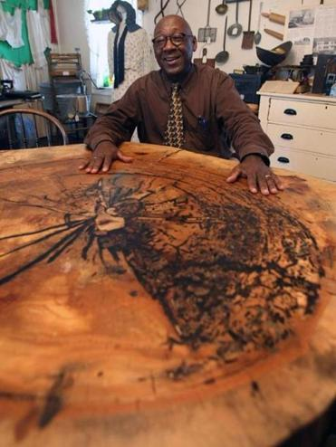Historical Society curator Willie Wilson with a slice of Brockton's original Liberty Tree.