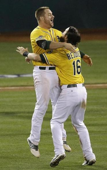 A's Stephen Vogt (left) and Josh Reddick celebrate after Vogt's single scored Yoenis Cespedes to win in the ninth.