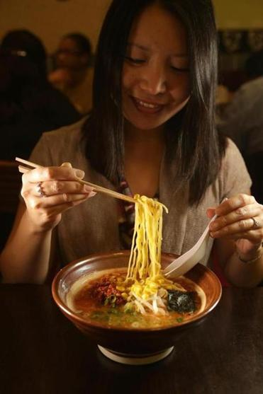 Carolyn Hann, of Washington, D.C., with a bowl of spicy miso ramen at Sapporo Ramen inside the Porter Exchange in Cambridge.
