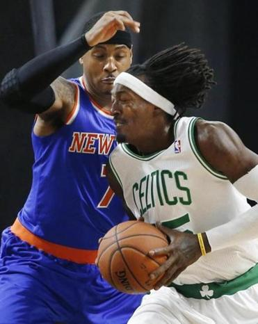Gerald Wallace of the Celtics has a hair-raising moment — and movement — as he drives on Carmelo Anthony.