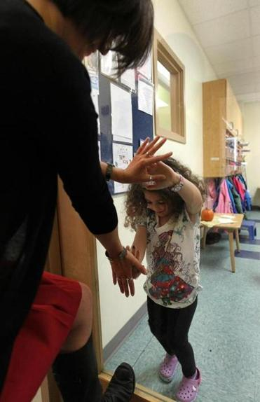 Director Kimberly Bouris and Ella Benvenuto, 4, exchange high-fives.