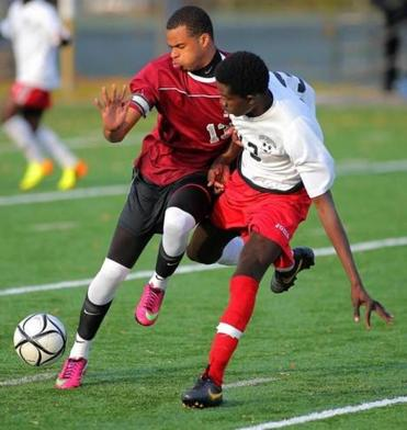 Dorchester's Valdo Jean Francois (right) and Madison Park's Claudio Teixeira fight for possession of the ball.